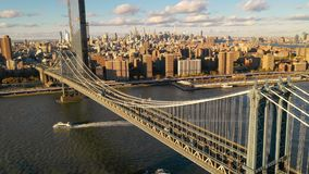 The Manhattan Bridge Crosses the East River in New York City as cruise boats move below