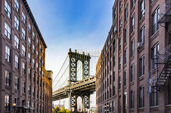 Manhattan Bridge Empire State. Famous Manhattan Bridge with Empire State in the arch seen from a narrow alley enclosed by two brick buildings on a sunny day, New Stock Photography
