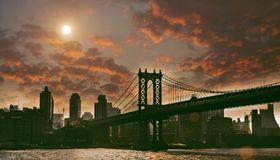 Manhattan bridge in the night. New York town, Manhattan bridge overcast day, night view red clouds and moon Royalty Free Stock Images