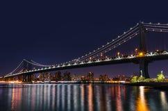 Manhattan Bridge At Night. Manhattan Skyline and Manhattan Bridge at night with reflections in East River. Manhattan Bridge is a suspension bridge that crosses Stock Photo