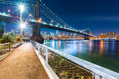 Manhattan Bridge by night. Viewed from John Street Park with Brooklyn Bridge and Lower Manhattan skyline in the background Royalty Free Stock Images