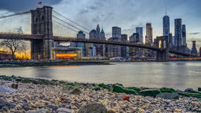 Manhattan Bridge and NYC Skyline at night. With reflection of  the skyline on East River Royalty Free Stock Photography