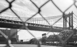 Manhattan Bridge seen through sport field fence, NYC, USA. Stock Photo