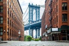 Manhattan bro mellan Manhattan och Brooklyn över East River som ses från en smal gränd inneslutad av två tegelstenbyggnader på a royaltyfri fotografi