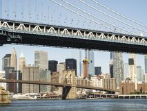 Manhattan bro och Brooklyn bro med Manhattan horisontbakgrund från Brooklyn tidigt på morgonen med blå den sh himmel och solen Arkivbilder