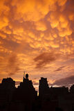 Manhattan buildings in silhouette with orange mammatus clouds at Royalty Free Stock Images