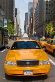 Manhattan buildings and taxis driving on a sunny day, New York City, USA Stock Image