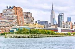 Manhattan dans un jour nuageux au rivage du Hudson Photo stock
