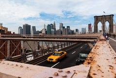Manhattan del puente de Brooklyn, Nueva York con el taxi amarillo en el primero plano imagen de archivo