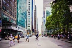 Manhattan gata med cykelryttare och gångare bland iconic b Arkivbilder
