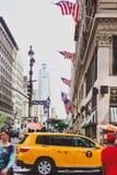 Manhattan gata med gula taxiar och gångare bland iconic b Arkivbild