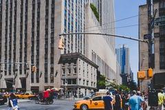Manhattan gata med gula taxiar och gångare bland iconic b Arkivfoto