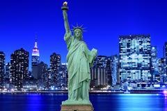 Manhattan horisont och statyn av frihet på natten Royaltyfria Bilder
