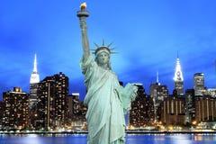 Manhattan horisont och statyn av frihet på natten Arkivbild