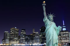 Manhattan horisont och statyn av frihet på natten Arkivbilder