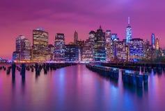 Manhattan horisont på natten med varicolored reflexioner i vattnet, USA Royaltyfri Bild