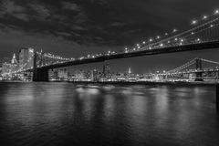 Manhattan Island at night in black and white. Photograph of the Brooklyn Bridge with the Manhattan brdge and the Empire State building beyond Royalty Free Stock Photography