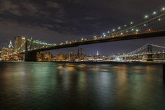 Manhattan Island at night. Photograph of the Brooklyn Bridge with the Manhattan brdge and the Empire State building beyond Stock Photos