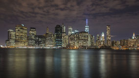 Manhattan Island at night. Photograph of Manhattan Island from Brooklyn with soft reflections of the city on the East River Stock Image