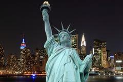 Manhattan linia horyzontu i statua wolności przy nocą Zdjęcia Stock