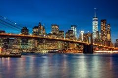 Manhattan med skyskrapor och Brooklin Bridge vid aftonen som är ny Fotografering för Bildbyråer