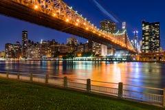 Manhattan Midtown som är östlig från Roosevelt Island med den Queensboro bron och Eastet River på skymning stad New York royaltyfri foto