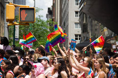 Manhattan, New York, June, 2017:audience with rainbow flag in The Gay Pride Parade and traffic light Royalty Free Stock Photo