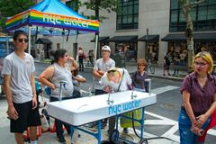 People drinking water at the 2018 New York City Pride Parade. Manhattan, New York - June 24, 2018: New York City Pride Parade commemorating the 49th anniversary royalty free stock photography
