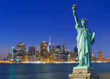 Manhattan at night and Statue of Liberty. Royalty Free Stock Photos