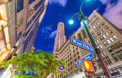 Manhattan at night. Street signs with tall skyscrapers on backhr Stock Image