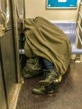 Manhattan, NY E.U. - 15 de fevereiro de 2018 a pessoa desabrigada dorme em um carro de metro foto de stock