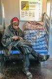 Manhattan, NY LOS E.E.U.U. - 19 de marzo de 2018 la persona sin hogar se sienta en un coche de subterráneo Fotografía de archivo libre de regalías