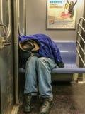 Manhattan, NY US - February 26, 2018 Homeless person sleeps in a subway car royalty free stock photo