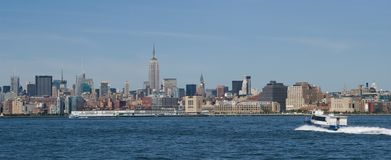 Manhattan panoramic. Panoramic skyline of Manhattan in New York city, U.S.A. Commuter boat sailing in foreground Stock Photography