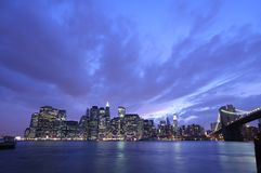 Manhattan skyline. Under a dramatic sky at night Stock Photos