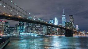 Manhattan skyline and Brooklyn bridge at night. Timelapse. Tall buildings on background, New York, NYC