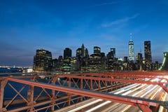 Manhattan Skyline from Brooklyn Bridge at Night. View of Manhattan Skyline Illuminated with Lights at Night from Brooklyn Bridge, Streaking Vehicle Head Lights Stock Photo