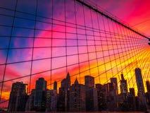 Manhattan-Skyline durch Brooklyn-Brücke bei Sonnenuntergang Lizenzfreie Stockfotografie