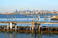 Manhattan Skyline and Pier. View of Manhattan skyline behind an old fishing pier stock photo