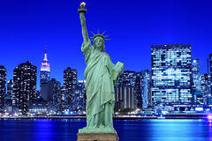 Manhattan Skyline and The Statue of Liberty at Night Royalty Free Stock Images