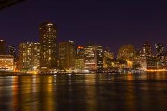 Manhattan skyskrapor med färgrika reflexioner i East River på natten Arkivbilder