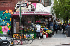 Manhattan street scene. NEW YORK, USA - May 05, 2016: Manhattan street scene. Bedford fruits and vegetables shop. New Yorkers in Manhattan in a hurry about their Royalty Free Stock Photos