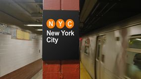 Manhattan Subway Approaches the Platform with New York City Sign. 8730 A Manhattan subway approaches the station near a hypothetical New York City identification stock video