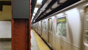 A Manhattan subway leaves the platform. A Manhattan subway train leaves the platform. Blank sign on pillar for customization stock video