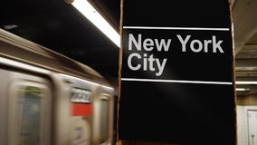 Manhattan Subway Leaves the Platform with New York City Sign. 8722 A Manhattan subway leaves the station near a hypothetical New York City identification sign on stock video footage