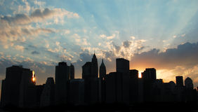 Manhattan Sunset. Downtown Manhattan Skyline with sunset.  There are rays of light emerging from behind the buildings.  The buildings are silhouetted with a Royalty Free Stock Photo