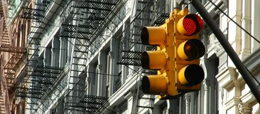 Manhattan Traffic Light. Red traffic light an Soho Facades with fire stairs stock photography