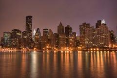 Manhattan van de binnenstad bij Nacht Stock Afbeeldingen