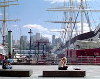 Manhattan Waterfront New York. A student reads a newspaper on the New York waterfront during lunch break in the Manhattan financial district stock photography