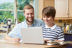 Manhemmet handleder Helping Boy With studier Royaltyfria Foton
